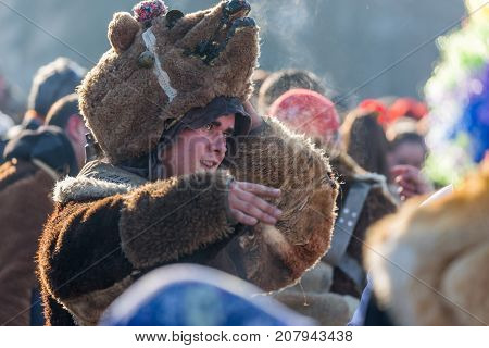 PERNIK BULGARIA - JANUARY 27 2017: Masked participant in fur bear mask is lifting his mask smiling and talking to his mates at Surva the International Festival of the Masquerade Games