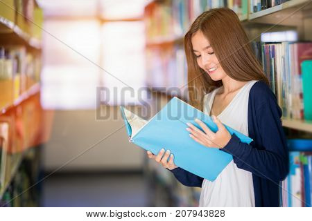 Asian student lady seek data for make a report in library in University for do her home work. Education student hight school concept