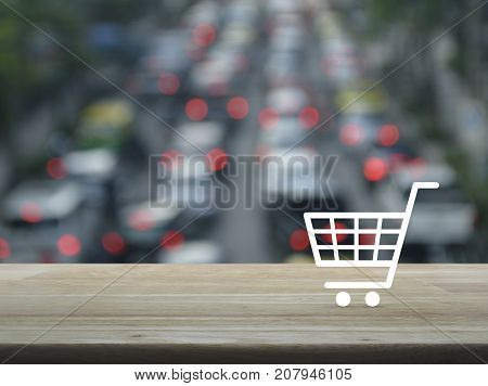 Shopping cart icon on wooden table over blur of rush hour with cars and road Shop online concept