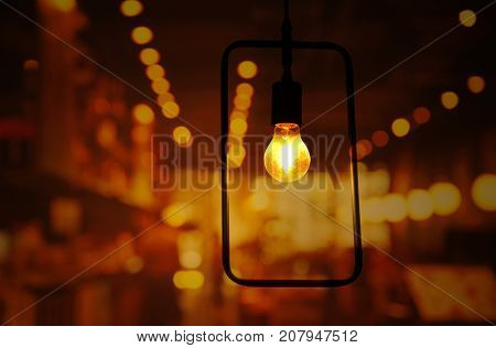bulb lamp light with rectangular metal frame with light bokeh night party in pub or bar abstract background