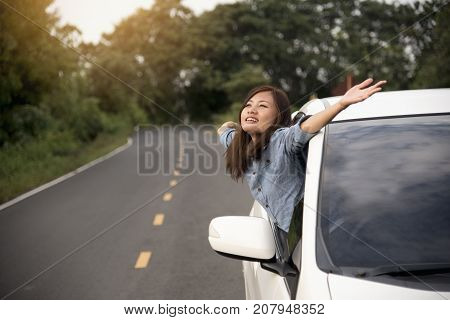 beautiful woman got new car. showing car key from window out of new car. car rental travel concept.