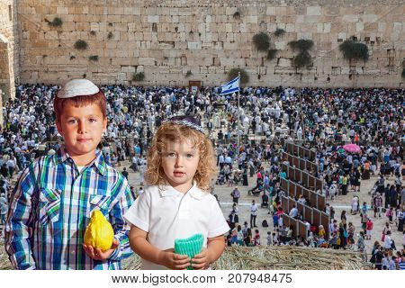The Western Wall of the Temple. Two beautiful Jewish boys in skull-caps with etrog. Autumn Jewish holiday Sukkot