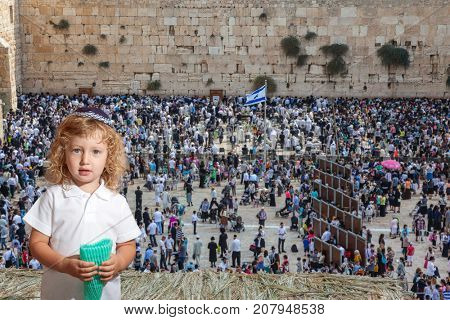 Beauteous little boy with blond side curls and blue eyes, in skullcap. Autumn Jewish holiday Sukkot.  The greatest shrine of Judaism is the Western Wall of the Temple