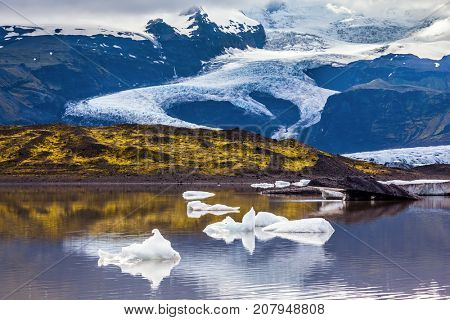 The cold lake with splinters of ice floes formed by thawed snow of glacier Vatnajokull.  Summer in Iceland. The concept of extreme northern tourism