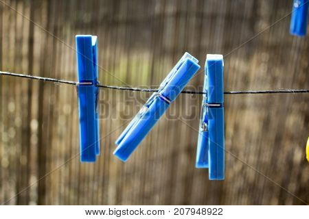 Blue plastic clothespins hanged on the rope