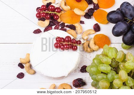 Grapes with soft cheese cashew nutsred currants dryed apricots and cranberries on white wooden background. Selective focus.