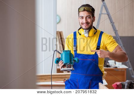 Young repairman carpenter working with power tools electric poli