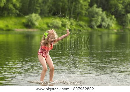 Litle girl playing in the water and making splash. Summer rest