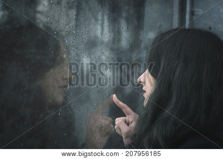 Woman looking on rainy window - Young brunette woman looking through a window covered with raindrops and touching the glass with her finger