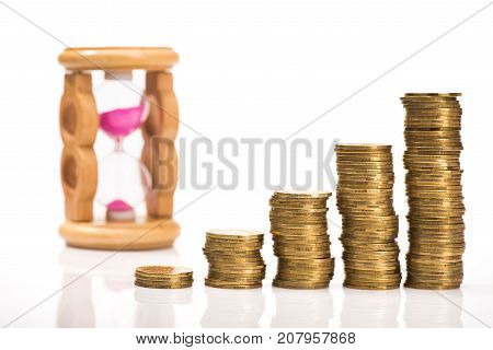 Pile Of Gold Coins And Sand Clock Isolated