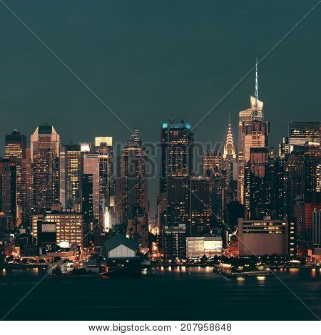 Midtown Manhattan skyline at dusk with street over Hudson River