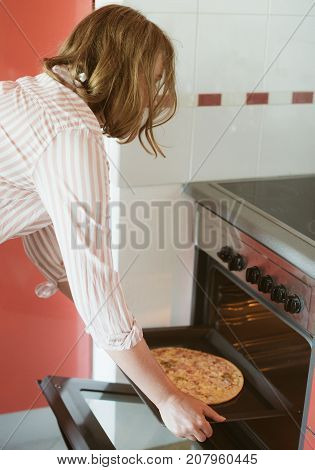 Woman preparing pizza bought in a store.