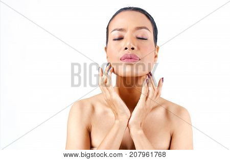Close up beautiful middle age Asian woman's face hands touching her chin isolated on white background beauty concept