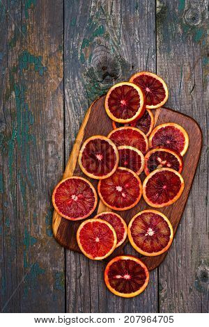 A burgundy mandarin on a wooden board is sliced with slices, top view