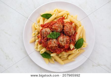 Pasta penne on a white plate on a white background