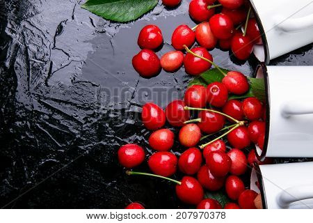 Scattered Cherry From Enamel Cups. Cherries In Iron Cup On Black Background. Healthy, Summer Fruit.