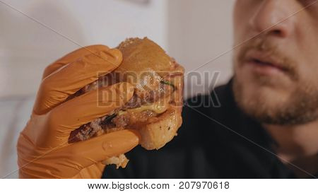 Hangry young man eating hamburger. Close-up remains of the hamburger. Hand in orange glove holding burger.
