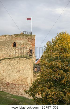 The ruins of the Livonia Order Castle was built in the middle of the 15th century. Bauska Latvia in autumn. Latvian flag on the top of the tower