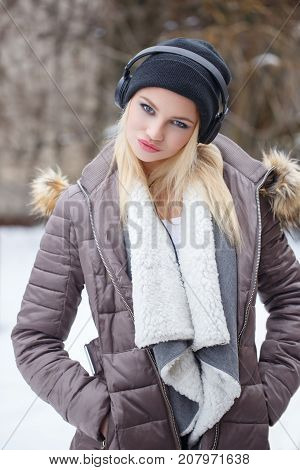 Young blonde woman in cap listening music by headphones at winter in snowy outdoor