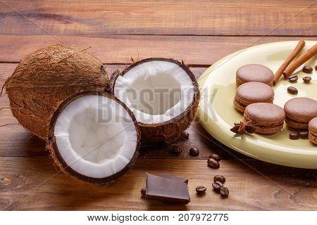 Coffee coconut macaroons chocolate cinnamon on wooden broun background