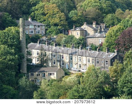 terraced houses amongst the trees on steep hills with old mill chimney in Hebden Bridge west yorkshire