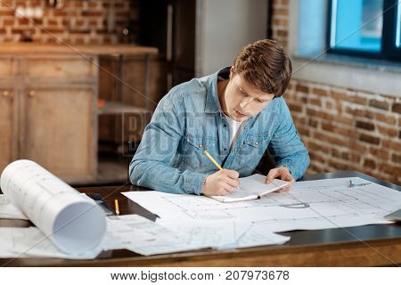 Analytical mind. Charming young engineer sitting at the table and making notes in the notebook regarding his project while working on the creation of a blueprint
