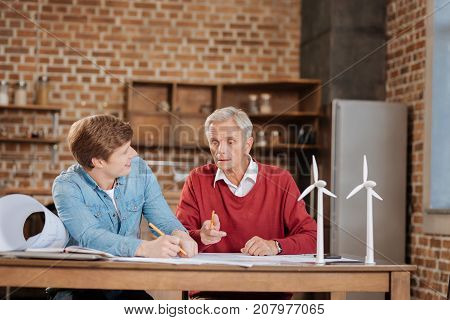 Sharing wisdom. Pleasant senior man sitting at the table next to his younger colleague and giving him pieces of advice while working together on a blueprint