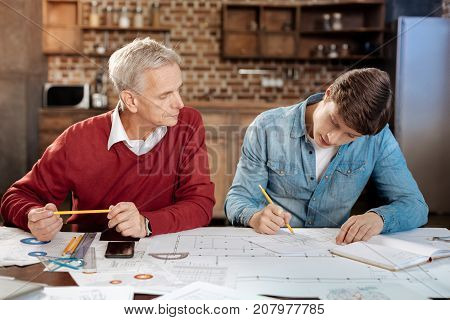 Best mentor. Pleasant senior man sitting next to his young colleague and watching him work on the creation of a blueprint, supervising him