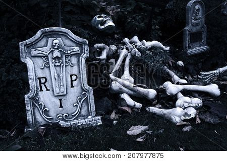 Halloween graveyard with tombstone and skeleton.