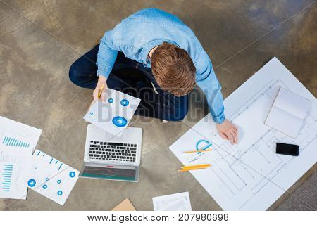 Engrossed in work. The top view of a charming young man sitting on the floor and holding a printout with chart in his hand while checking something on blueprint