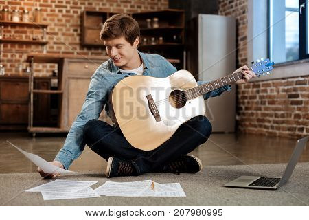 Gifted musician. Handsome young man sitting on the floor, holding a guitar and looking through a musical score in his hand