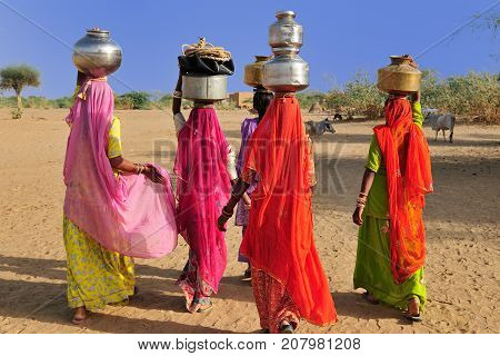 Indian ethnic women going for the water in well on the desert. Rajasthan India. Thar desert near Jaisamler.