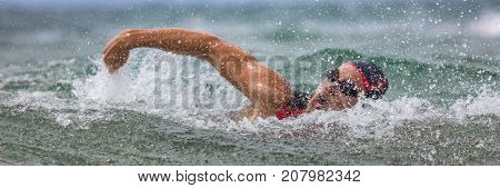 Triathlete man swimming freestyle crawl in ocean panorama banner. Male triathlon swimmer swimming in professional triathlon suit training for ironman on Hawaii.