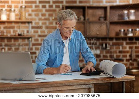 Thorough work. Grey-haired senior man in spectacles using a calculator to do math while drawing a blueprint with a pair of compasses