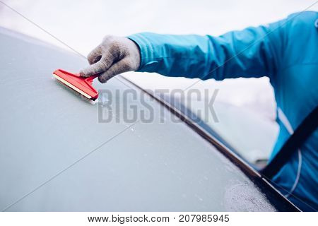 Woman Scraping Frozen Front Car Windshield