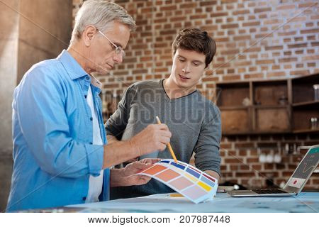 Making choices. Two pleasant male colleagues standing near the counter and choosing a color from a color chart while the older man pointing at his choice with a pencil