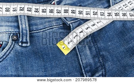A blue woman jeans and ruler concept of diet and weight loss. Jeans with measuring tape. Healthy lifestyle dieting fitness. Weight control. Successful diet. Reducing excess weight
