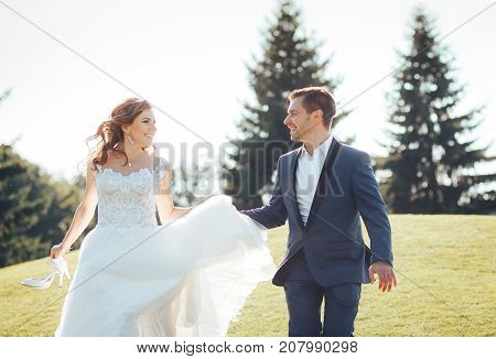 Happy and smiling newlyweds running outdoors holding hands