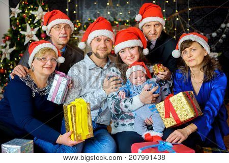 a big happy family in caps of Santaclaus celebrates Christmas gives each other presents and has fun