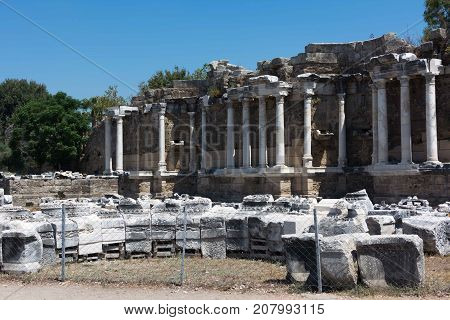 Fountain of Nymphaeus in Side, Turkey. Beautiful ruins of a great structure against the blue sky. An unusual photo.