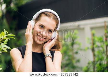 People leisure and technology concept - Attractive young woman listening to music on the music player in outdoors. Hipster girl enjoying the tunes in her earphones in the morning park. Lens Flare.