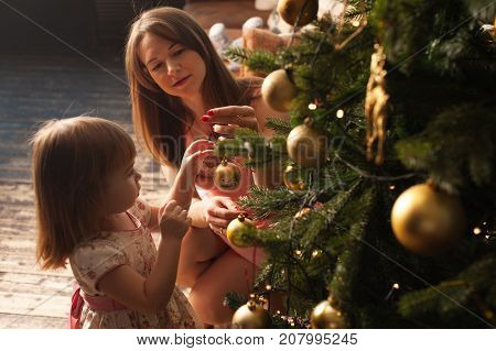 Happy smiling mother and little daughter decorating Christmas tree together. Loving parent and child having fun at home. Merry Christmas and Happy holidays.