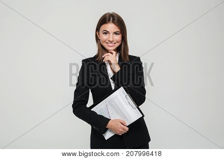 Portrait of a smiling satisfied businesswoman in suit holding clipboard with documents and looking at camera isolated over white background