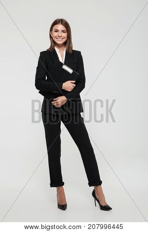 Full length portrait of a happy smiling businesswoman in suit holding clipboard and looking at camera isolated over white background