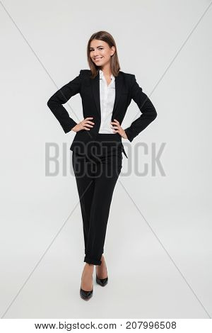 Full length portrait of a confident young businesswoman in suit standing with arms on hips and looking at camera isolated over white background