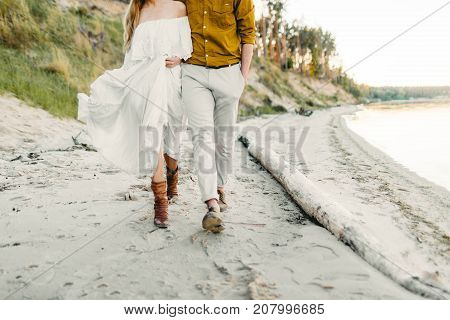 A young couple is having fun and walking on the sea coastline. Newlyweds looking at each other with tenderness. Romantic date on the beach. Wedding. Artwork, soft focus