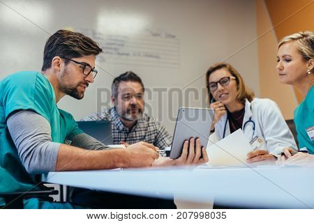 Team of medical staff having morning meeting in boardroom. Doctors and nurses looking at digital tablet.