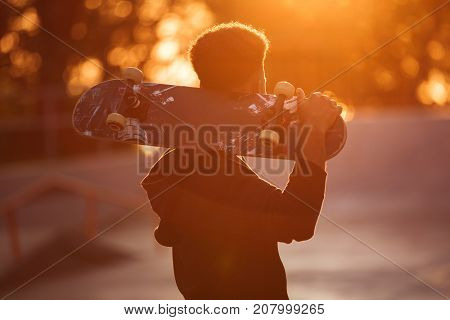 Young skateboarder man holding skateboard on his shoulders at public park