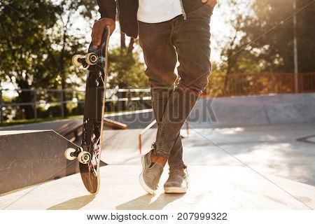 Cropped image of a young african man skateboarder standing with a skateboard at sunset city park