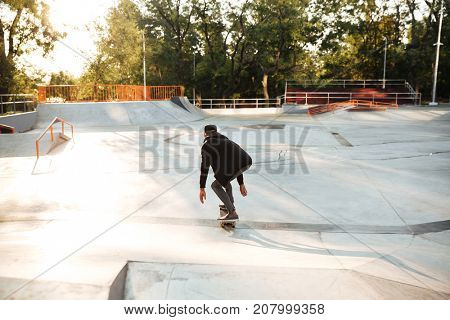 Young afro american skateboarder skating on a concrete skateboarding ramp at the skate park